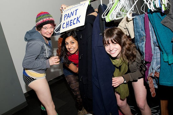 Organizer Mallory Nezam (center) helps check in pants.