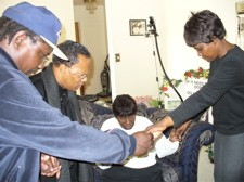"The family of Charles ""Cookie"" Thornton prays in the home the day after the shootings. - PHOTO: CHAD GARRISON"