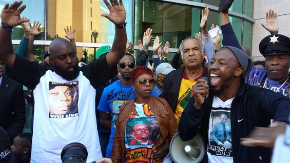 """Michael Brown Sr. (L) gives the """"Hands Up, Don't Shoot"""" sign during a protest with Lesley McSpadden, Michael Brown's mother, and Pastor Carlton Lee. - JESSICA LUSSENHOP"""