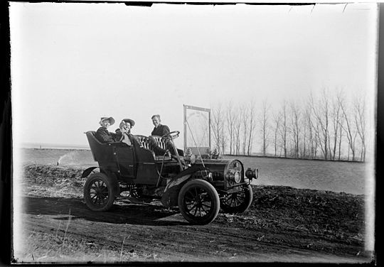 A young man and his two lady friends take a spin in the new-fangled invention of the day, the gas-powered automobile. - COURTESY OF JOHN FOSTER