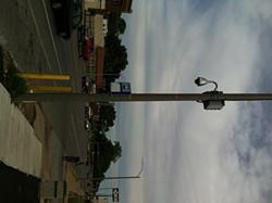 A camera along Natural Bridge road hangs from a street light.
