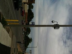 A camera along Natural Bridge road hangs from a street light.