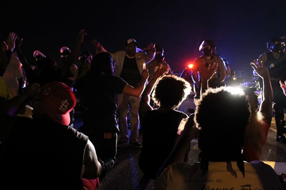 Protesters kneel down and put their hands up in front of police. - RAY DOWNS