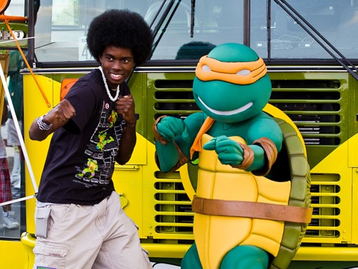 Brian McKinley, 18,Poses with Michelangelo in front of the Turtles Party Bus. McKinley  drove 7 hours from Huntsville Alabama to see the Teenage Mutant Ninja Turtles, Having purchased TMNT figures and apparel since he was 2, Brian remarked that the collection inside the party bus was much smaller than his. - PHOTO: STEW SMITH