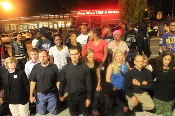 Several clergy members kneel down in prayer in front of the Ferguson Police Department. - RAY DOWNS