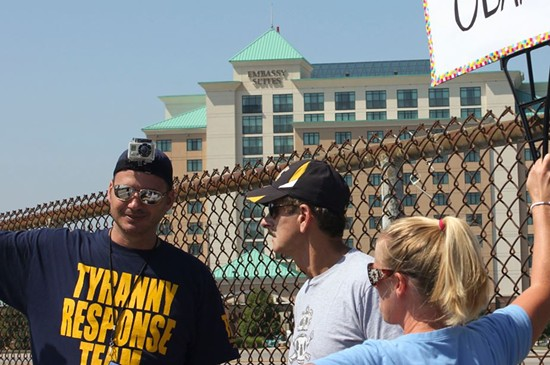 Marc Messmer, left, talks with another protester during an Overpasses for Obama's Impeachment rally on August 24, 2013. - DANNY WICENTOWSKI