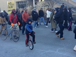 Finn McNamee, eight, rides his unicycle in the MLK parade yesterday. Big photos below.