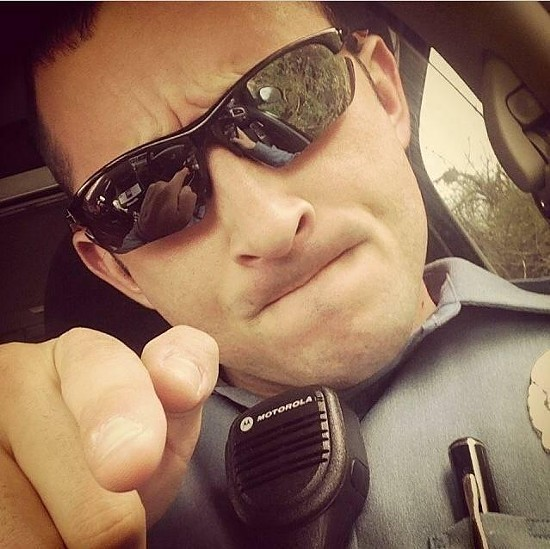 Ferguson police officer Justin Cosma arrested two journalists on August 13. - TWITTER/RYANREILLY