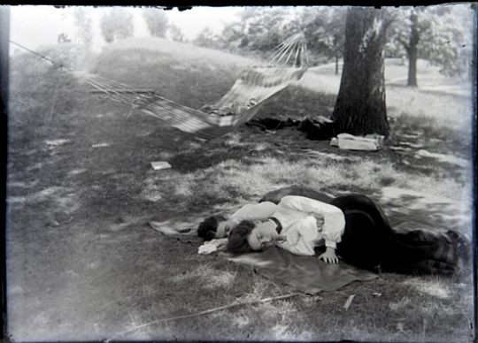Two women take a nap in a St. Louis park circa 1900. - COURTESY OF JOHN FOSTER