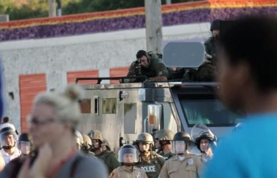 An officer on the scene in Ferguson peers down the scope of his rifle at an unarmed, peaceful crowd. - DANNY WICENTOWSKI