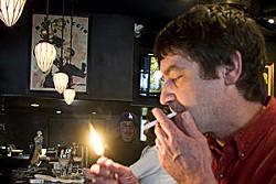 Hannegan lighting up at one of his favorite haunts, Herbies' Vintage '72. - PHOTO: JENN SILVERBERG