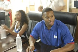 Umenyiora signing autographs on a USO tour. - WIKIMEDIA COMMONS
