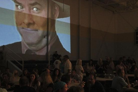 A projection of David Koechner's most famous role, Champ Kind, watched as the crowd began to fill the gym grade-school gym.