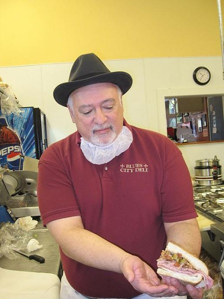 Vince Valenza of Blues City Deli shows off his muffuletta sandwich. - ROBIN WHEELER
