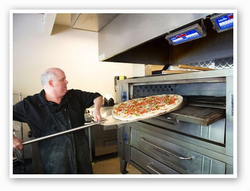 A pizza into the oven at King Louie's Empire Deli & Grill | Corey Woodruff