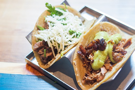 Carne asada taco beside a chile roasted duck taco with crisp pork-belly carnitas and avocado serrano sauce.