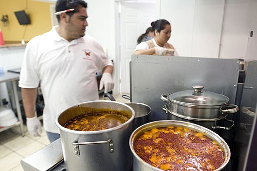 Jose in the kitchen with Vivian Acatecas. Menudo is stewing on the stovetop. See photo slide show here. - PHOTO: JENNIFER SILVERBERG