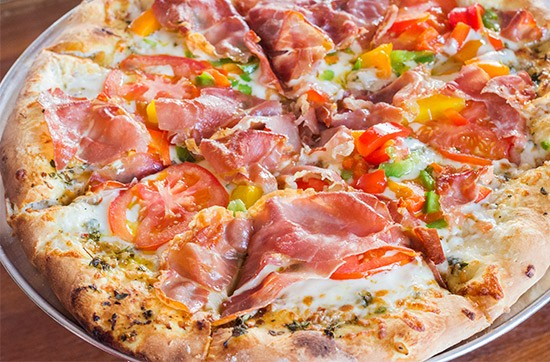 """Yaqui's """"Bianca"""" pizza with mozzarella, herb-infused oil and the addition of prosciutto and peppers. 