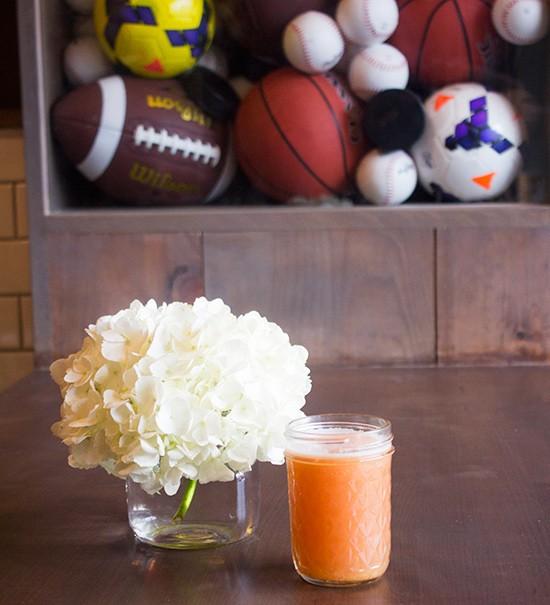 "A half pint of ""Hugo's Jugo"" juice with pineapple, watermelon, apple and orange."