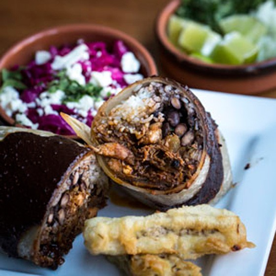 Mole poblano burrito, with slow cooked turkey in a blend of chile peppers, peanuts, mole, crema fresca, black beans and rice. | Jennifer Silverberg