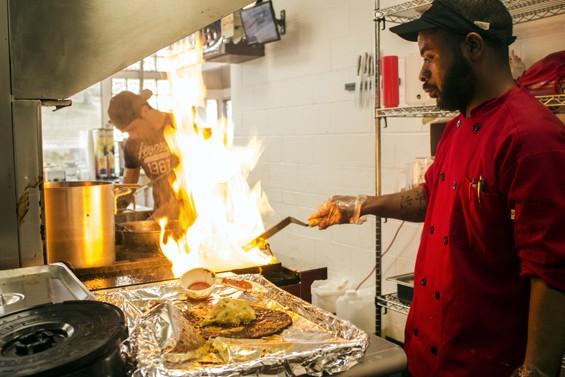 Fort Taco cook Montel Bosley flame grills tortillas for enchiladas.   Mabel Suen