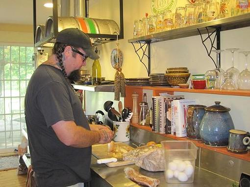 Herren preparing his savory bread pudding in his kitchen. - ROBIN WHEELER