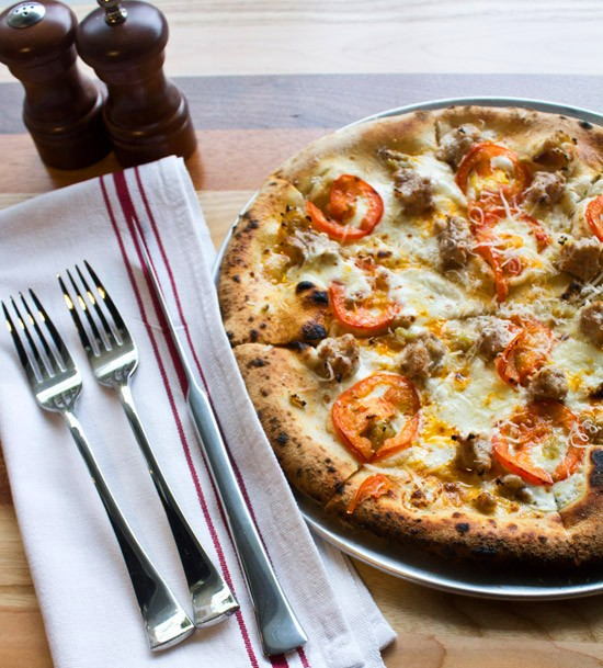 Spicy diavolo pizza with heritage Berkshire sausage, spicy marinated tomatoes, housemade mozzarella, chile oil and fresh Parmesan. - MABEL SUEN