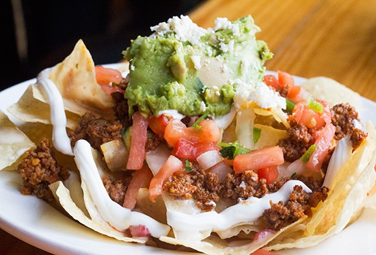 """Loaded Nachos"" with picadillo beef."