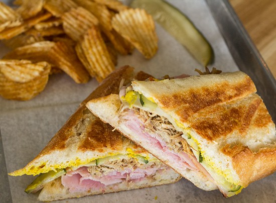 The Cuban sandwich on a baguette with ham, roast pork, Swiss, pickle and mustard.