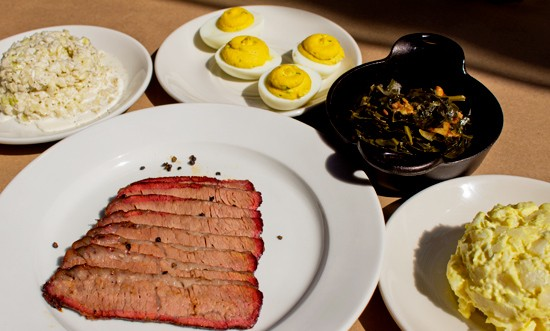 Smoked brisket with sides of cole slaw, deviled eggs, bacon braised greens and potato salad. - MABEL SUEN