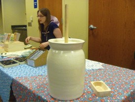 Two iconic symbols of Little House on the Prairie: A sunbonnet (worn by Pudd'nhead Books children's buyer Melissa Posten) and a butter churn.