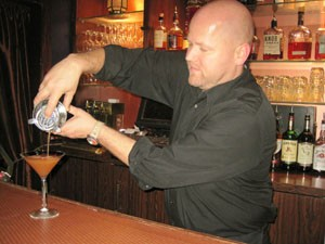 John Kennedy mixes some holiday cheer in a glass. - KRISTIE MCCLANAHAN