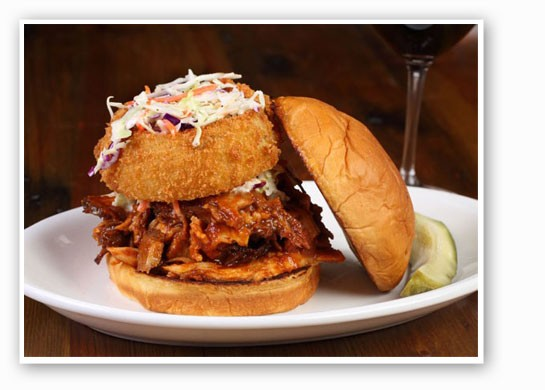 """The """"Big Andy:"""" brisket, turkey, pork, chicken, slaw and an onion ring served on a toasted sweet Hawaiian roll. 