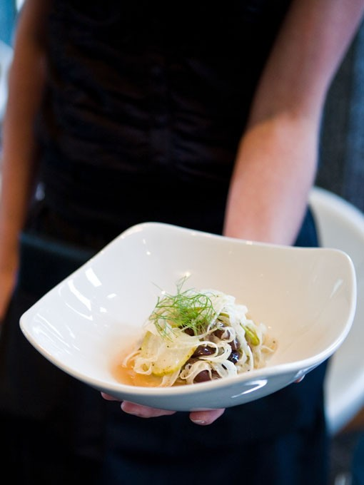 An Eclipse server holds a shaved fennel and pear with olives salad. - PHOTO: STEW SMITH