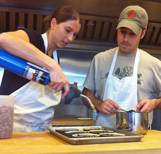 Agi Groff takes a torch to a batch of ganache-covered tarts as husband Aaron looks on. - HOLLY FANN