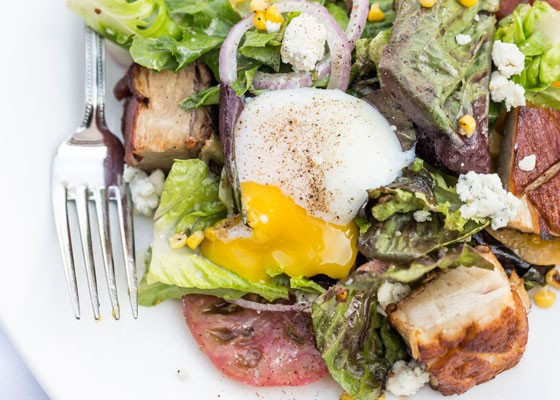 801 Chophouse Salad with mixed baby lettuces, roasted corn, tomato, shaved red onion, braised pork belly, maytag blue cheese crumbles and herb vinaigrette. topped with poached egg. | Jennifer Silverberg