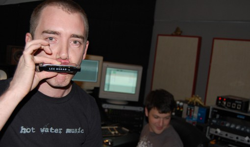 Bryan Clarkson playing the harmonica he uses on the album. Recording engineer Brian Scheffer is in the background.