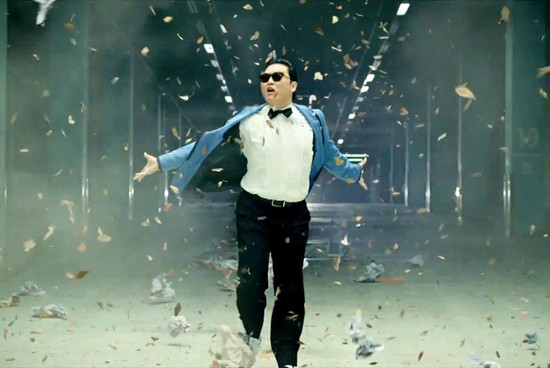 PSY, RUNNING THROUGH ALL THE AMERICAN DOLLARS FLYING RAPIDLY IN HIS DIRECTION.