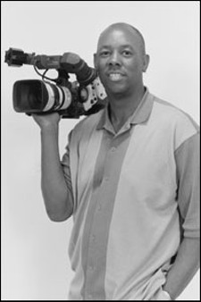 Art Holliday, TV news anchor and director of an in-production film,  Johnnie Be Good - IMAGE VIA