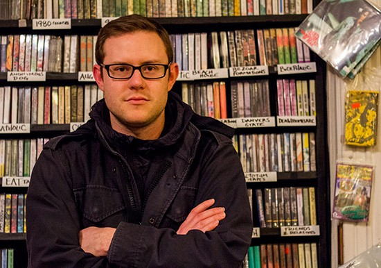 Nathan Cook stands among the wall of tapes at Apop Records. - MABEL SUEN