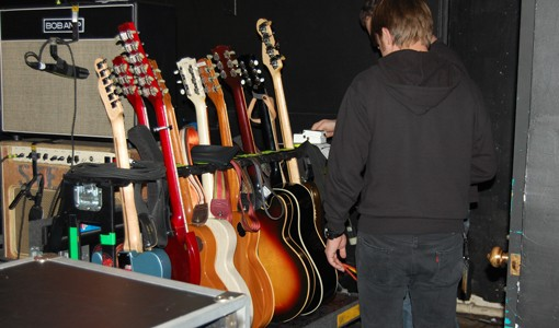 Seven guitars and one bass, backstage.