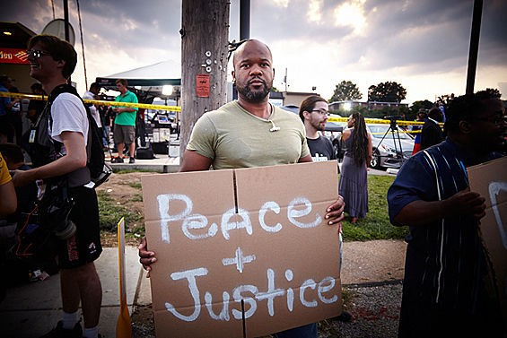A protester in Ferguson calls for justice and peace. - STEVE TRUESDELL