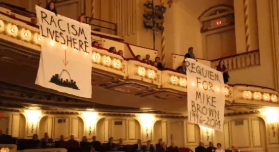 Singing protesters display banners at Powell Hall. - SCREENSHOT FROM THE YOUTUBE VIDEO.