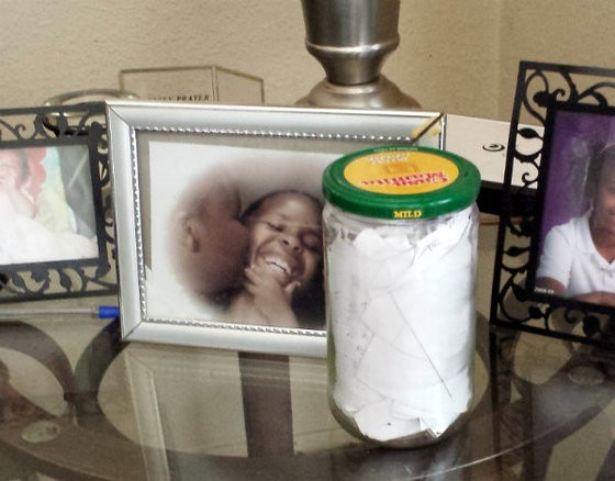 A jar full of Mike Brown's rap lyric ideas, written on tiny slips of paper, next to family photos at his grandmother's house. - JESSICA LUSSENHOP