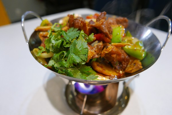 The Dry Pot chicken is served over the flame. - DESI ISAACSON