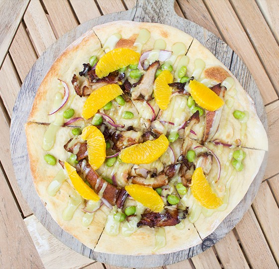 """Asian Chicken"" pizza with soy-garlic marinated chicken, sesame oil, red onion, edamame, orange segments and wasabi aioli. 