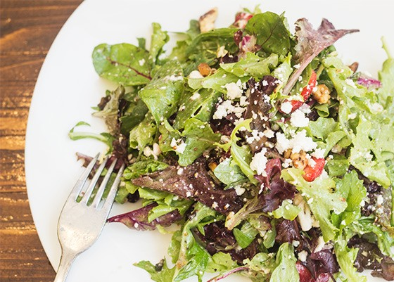 Strawberry fields salad with spring mix, strawberries, feta cheese, red onion, sage, mint, candied walnuts and white-balsamic vinaigrette.