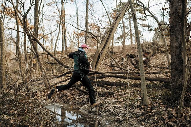 Rob Connoley leaps over a stream during a recent foraging trip to Forest Park. - VIRGINIA HAROLD