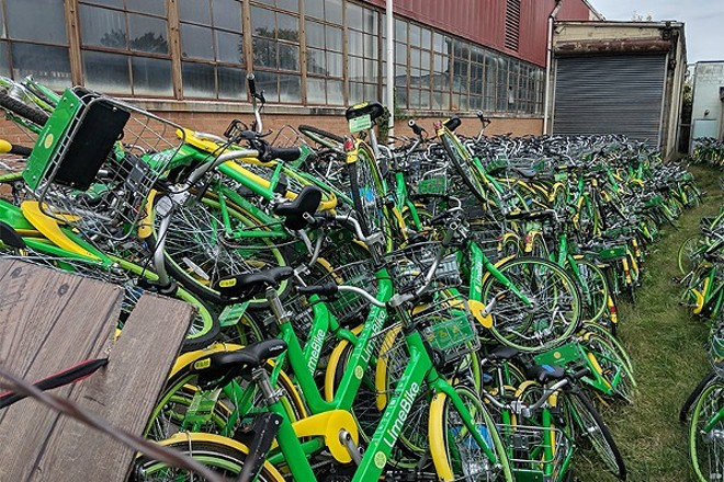 Dozens of Lime damaged bikes awaiting repair turned up in an alley behind a warehouse in August. - DANNY WICENTOWSKI