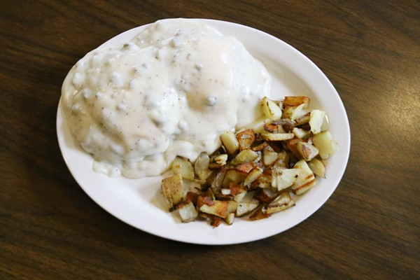 The Big Biscuit Breakfast features homemade buttermilk biscuits topped with sausage patties, two eggs. cheese and sausage gravy. It's served with potatoes. - CHELSEA NEULING